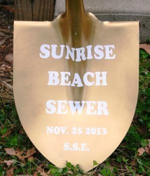 gold shovel with words Sunrise Beach sewer on it