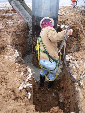 man in trench pouring concrete